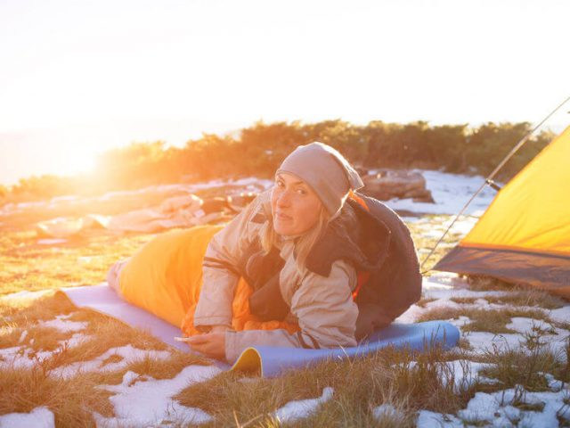 The girl lying in a sleeping bag on the nature