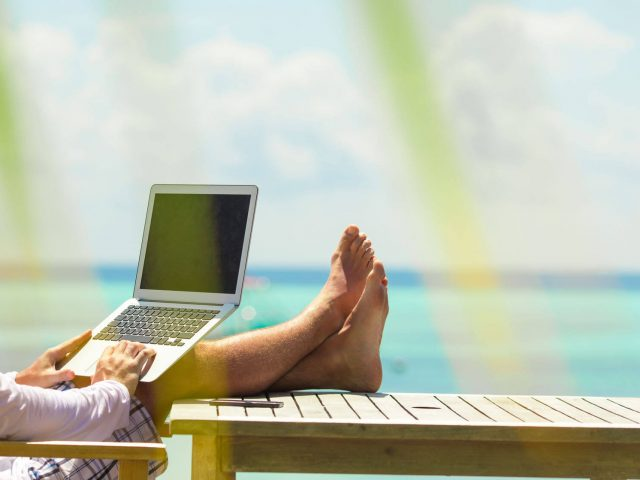 Young man with computer during tropical beach vacation
