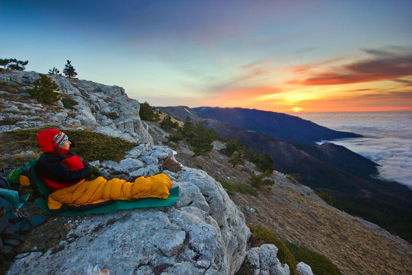 girl sitting in yellow sleeping bag on a cliff