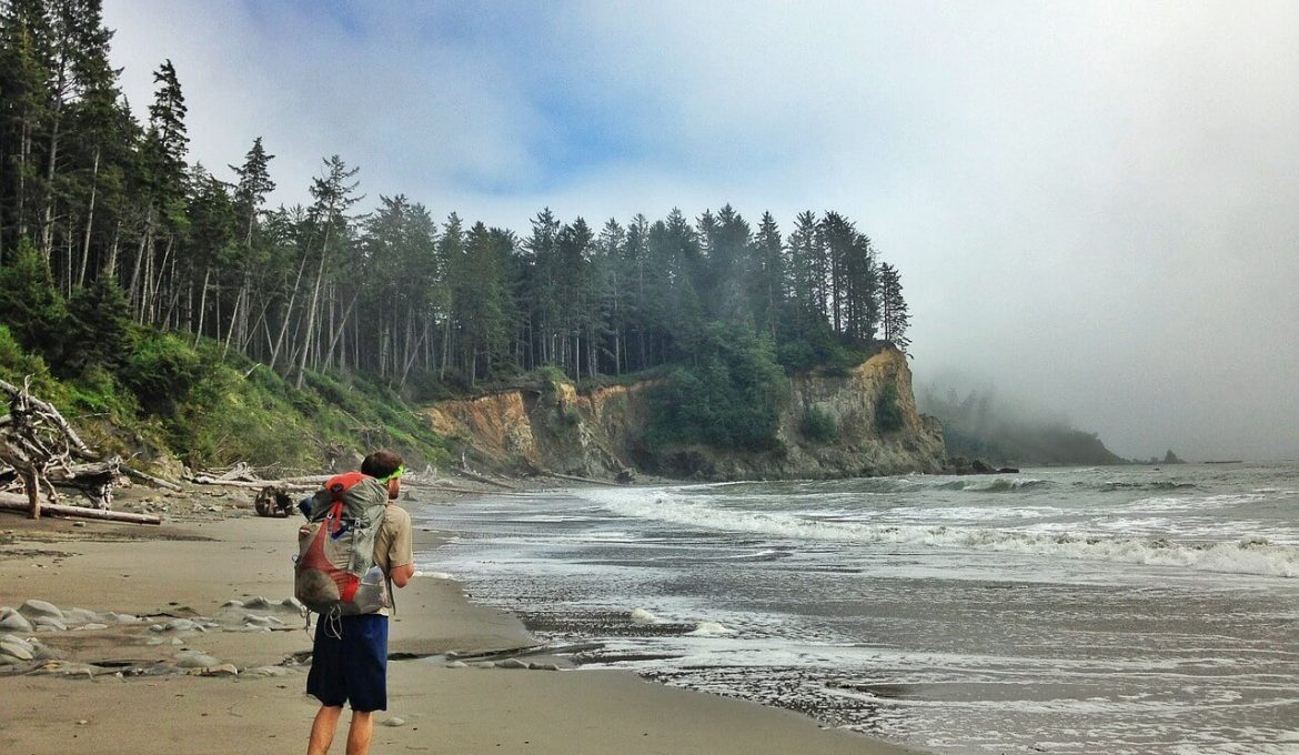 hiker with big backpack on the beach