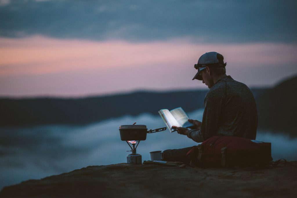 person sitting reading book near camping stove