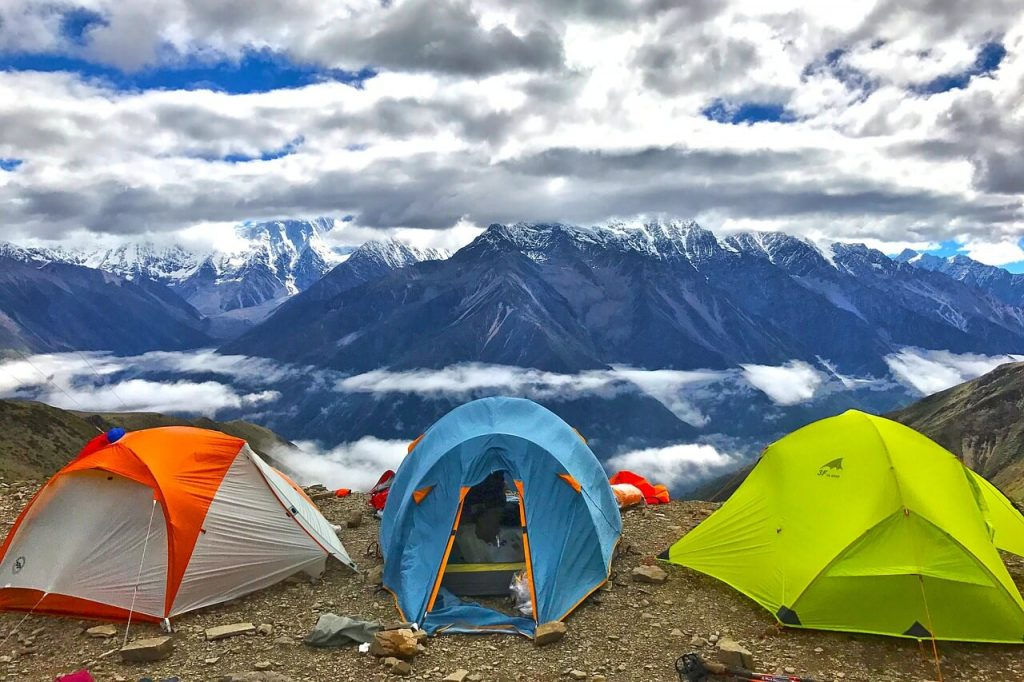 three backpacking tents on mountain peak with snow