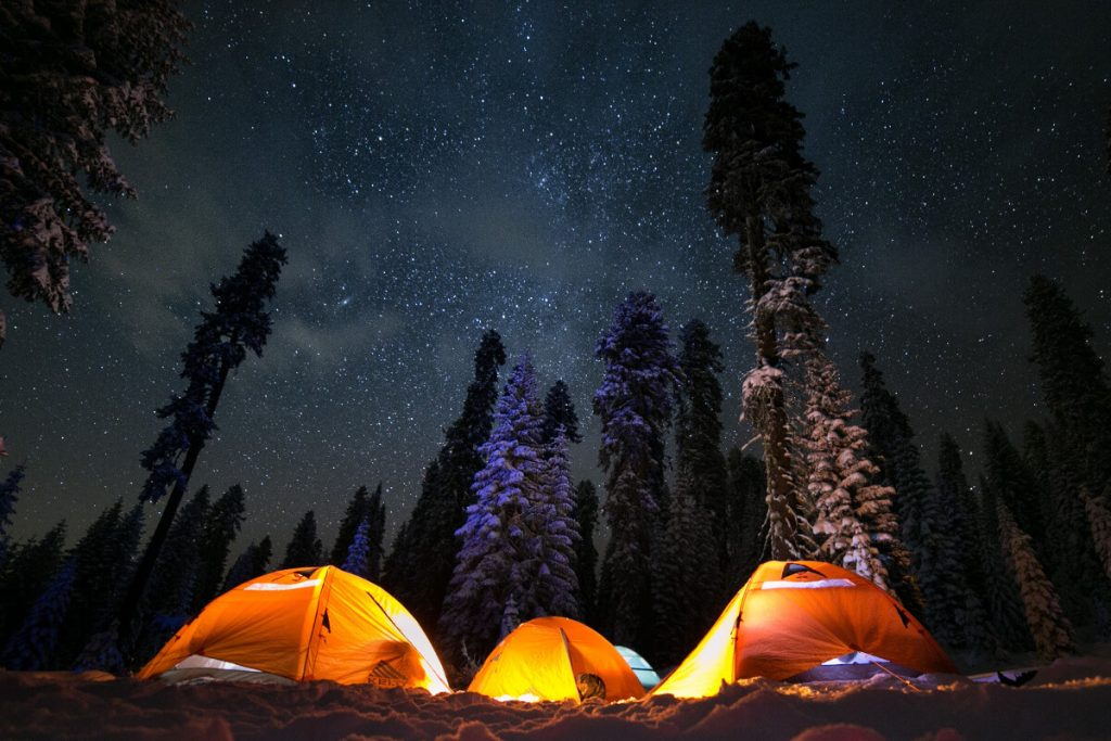three camping tents under stars