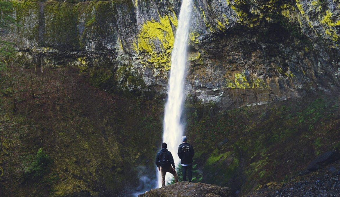 two hikers very near to waterfall