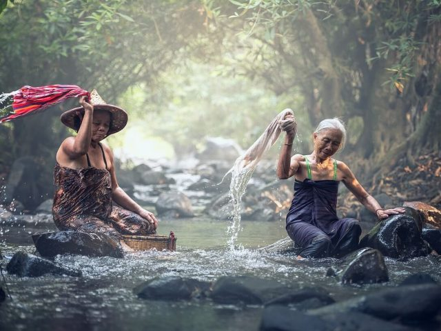 two ladies washing clothes in river