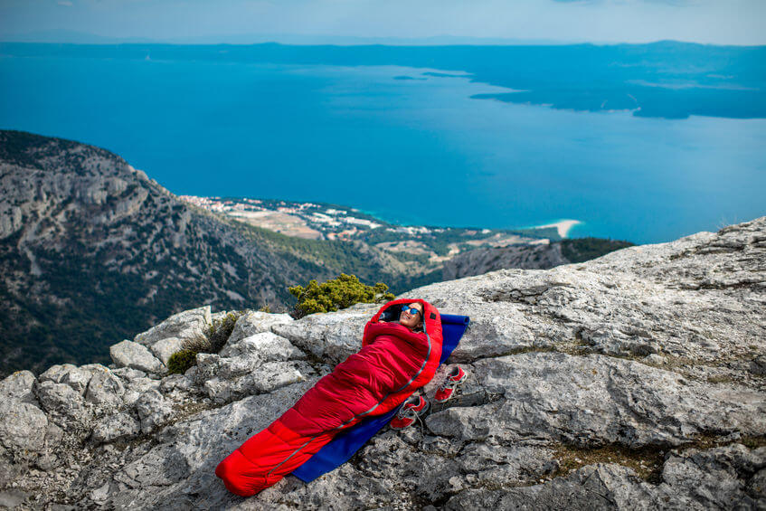 woman lying in red sleeping bag on the rocky mountain
