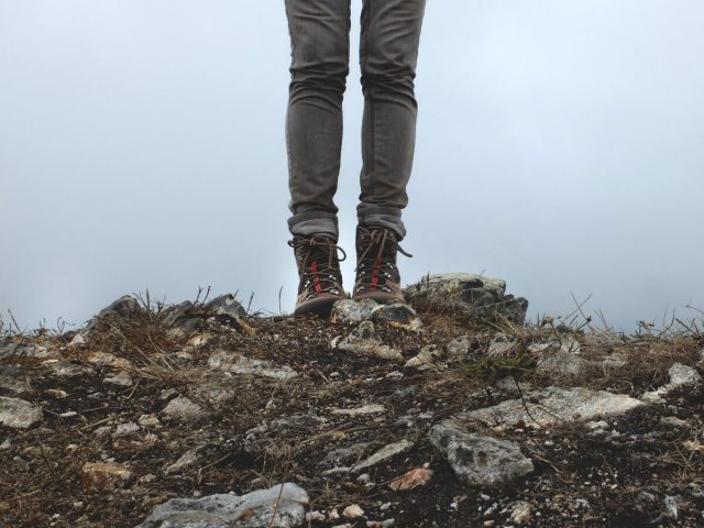 woman wearing hiking boots and jeans - standing on rocks