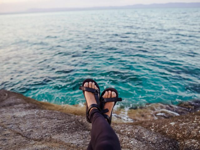 woman wearing hiking sandals near ocean