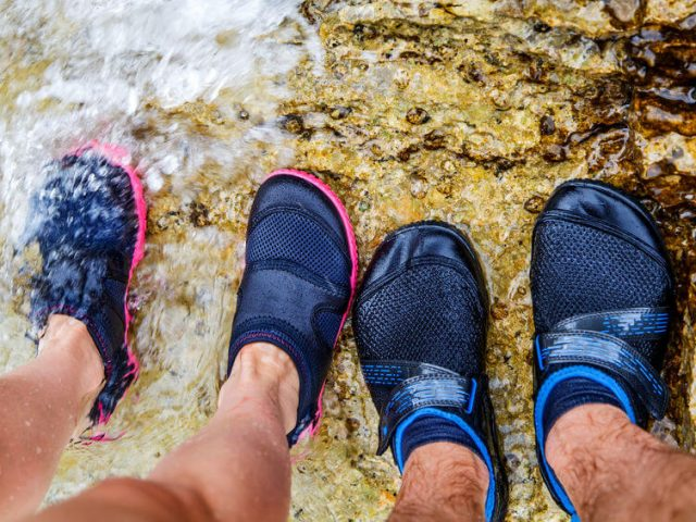 couple in water shoe standing on rocky beach