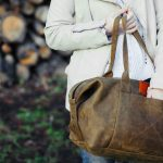 girl with a leather duffel bag for travel