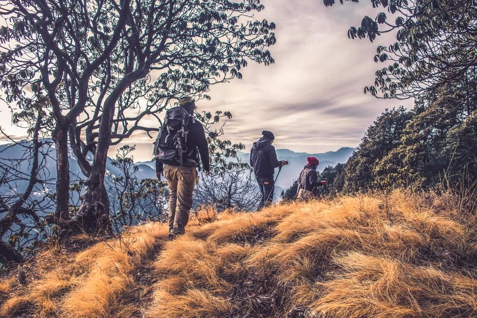 people with backpacks hiking on high mountain