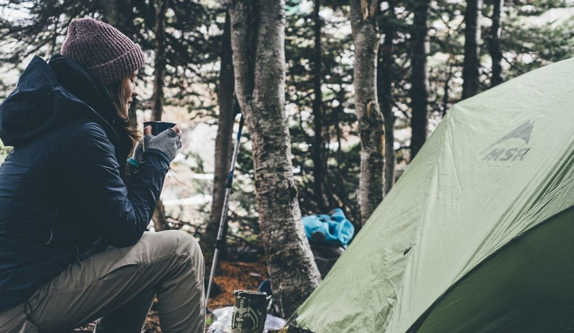 girl drinking coffee in campsite