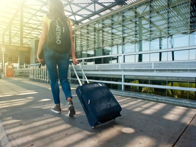 women traveling with carry-on luggage