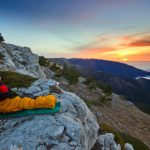 girl sitting in yellow sleeping bag with liner on a cliff