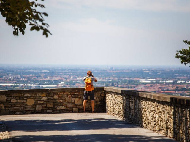 tourist stands with backpack on the viewing platform in Italy