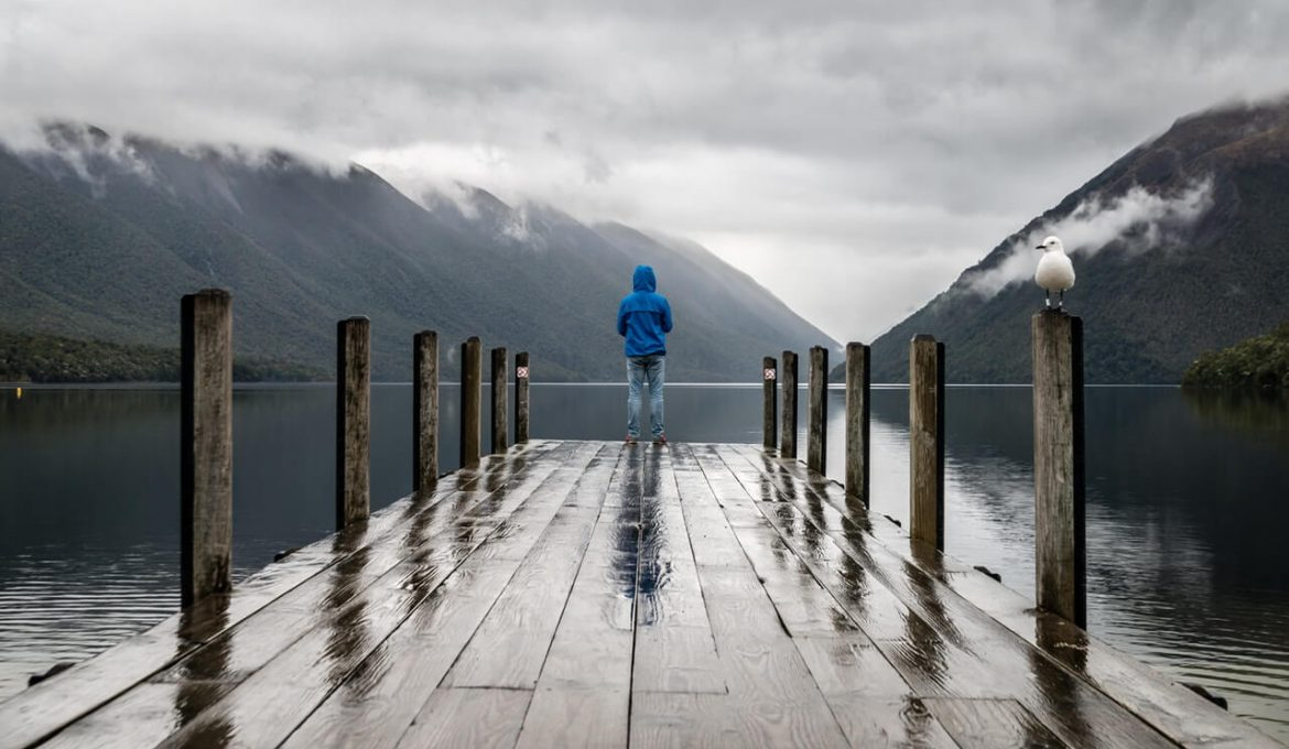 person standing on brown wooden dock in the rain