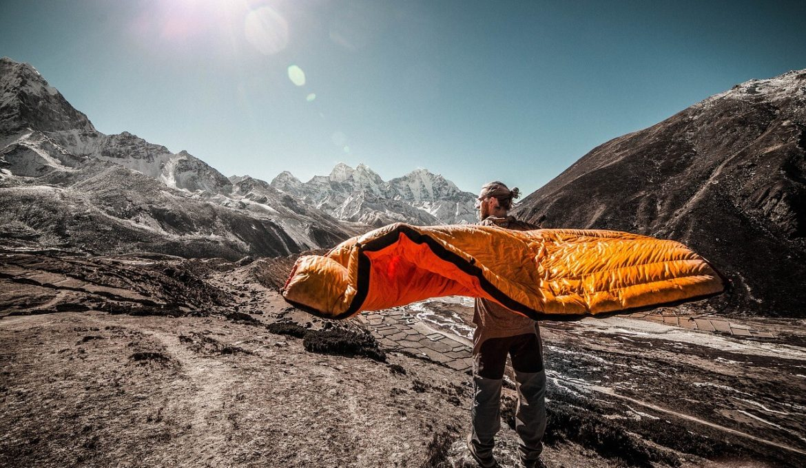 traveler holding sleeping pad in mountains