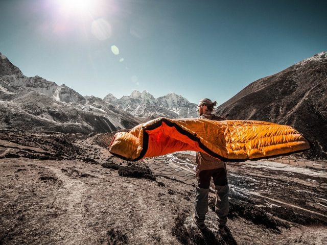 traveler holding sleeping bag in mountains