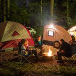 family camping at night with campfire