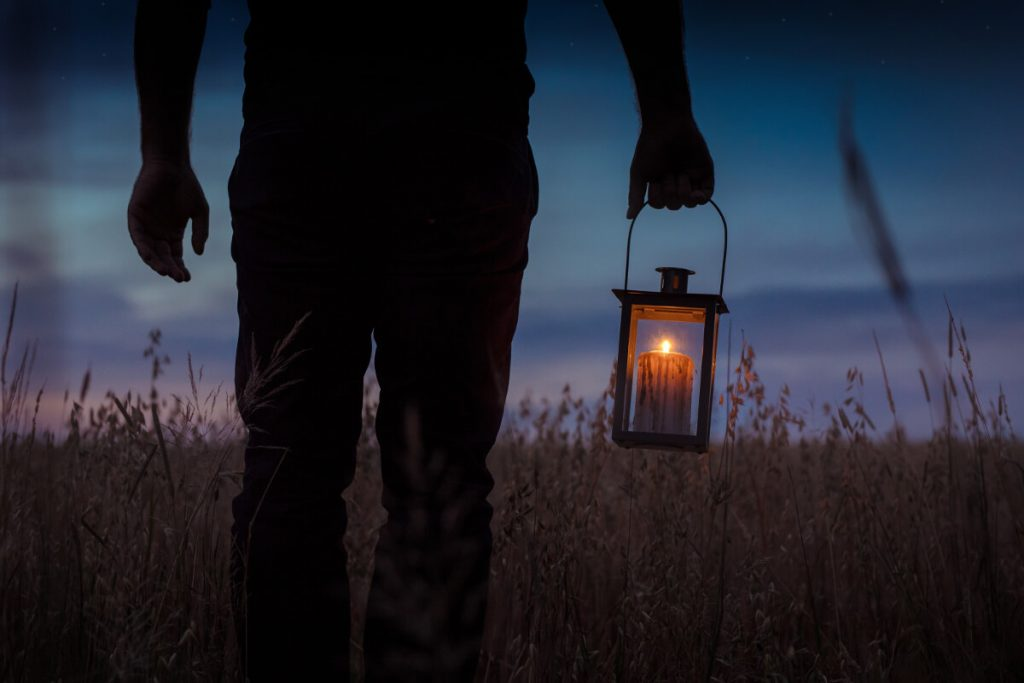 silhouette photo of man carrying candle camping lantern