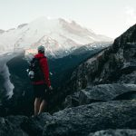 traveler with rain jacket and backpack standing on cliff