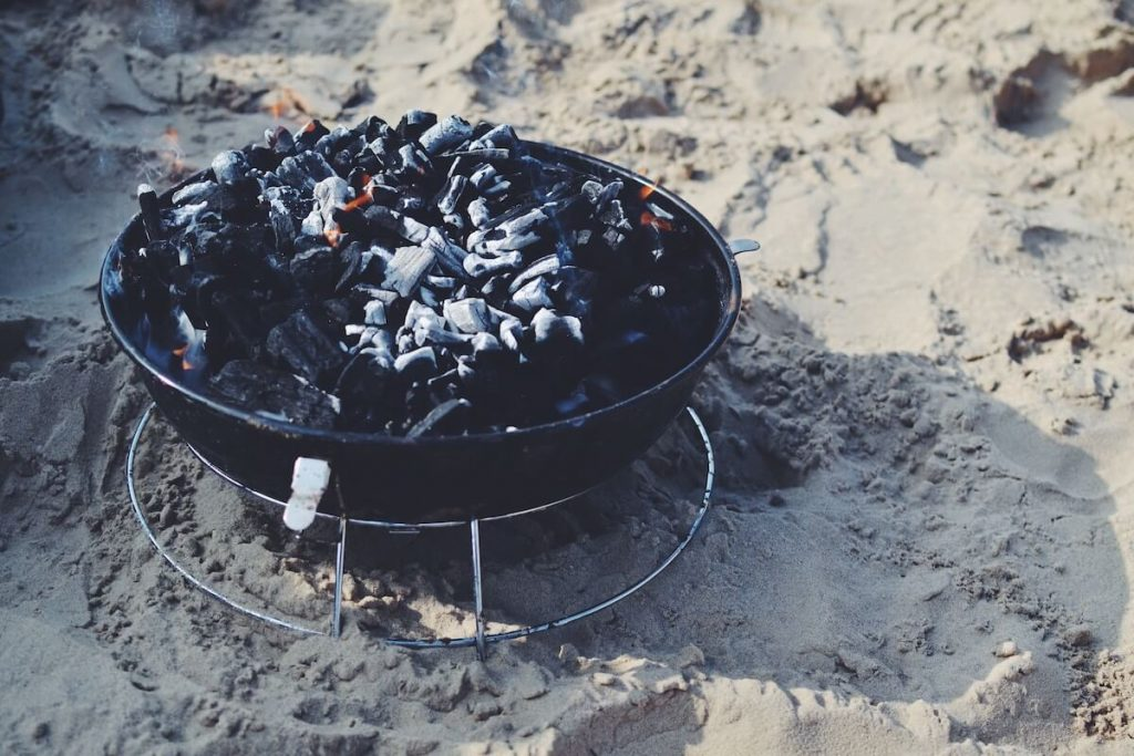 charcoal grill set in sand