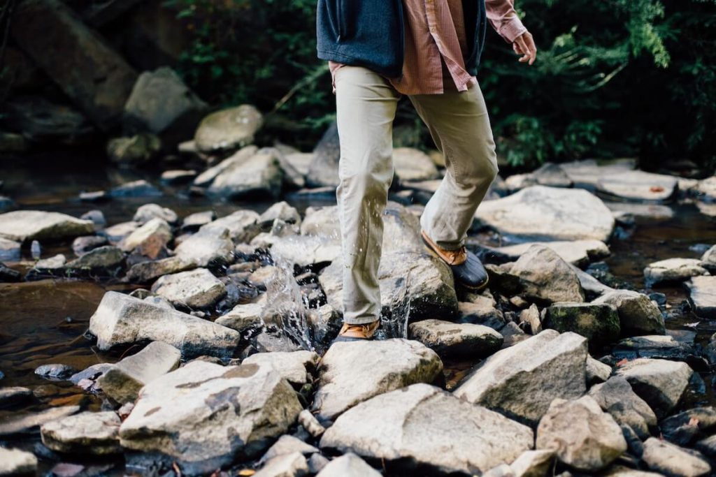 man in boots standing on rocks