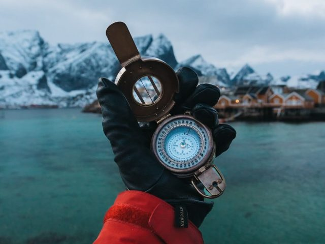 man in gloves holding a compass