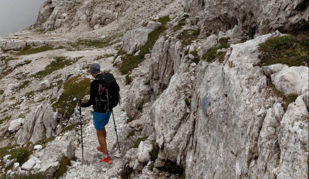 man with trekking poles hiking
