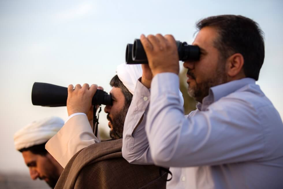 three man with binoculars