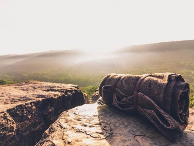 travel blanket placed on rocks