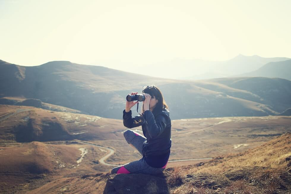 women in mountains with binoculars