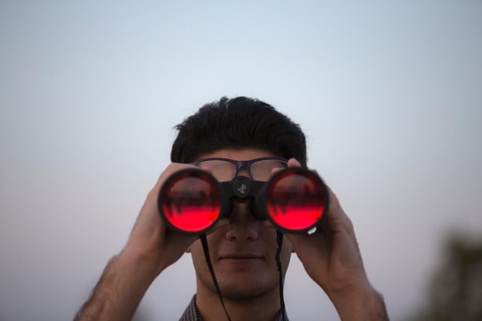 young man looking in binoculars