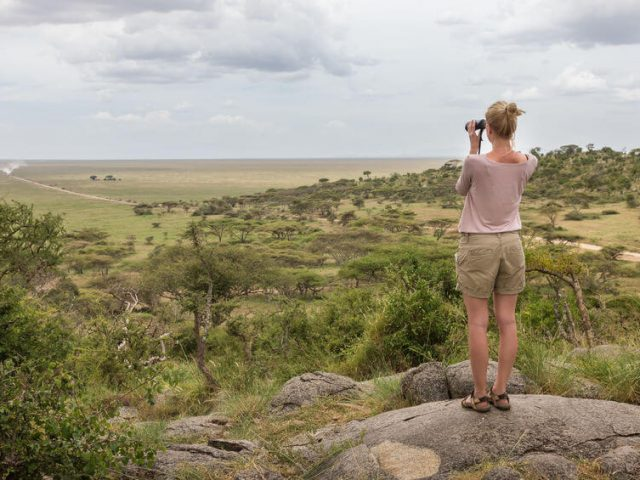 female tourist looking through binoculars on African safari