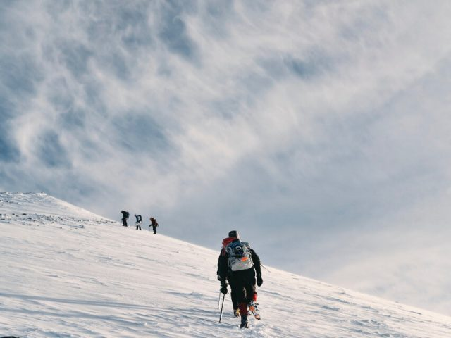 men climbing snow covered mountain in cold weather