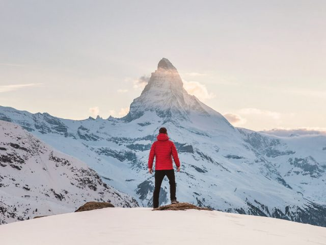 person in red packable down jacket standing on snowy mountain