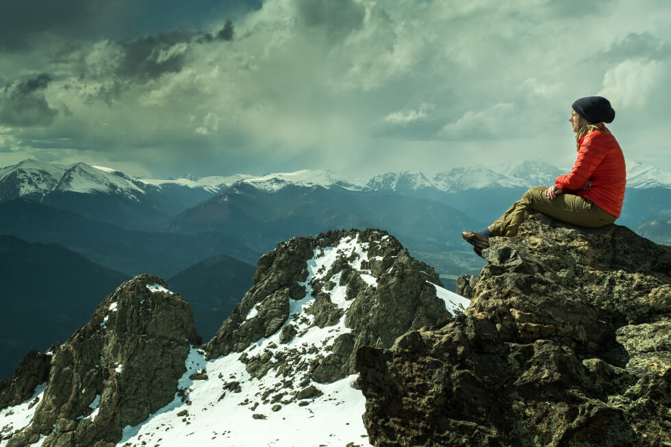woman sitting on rock across snow covered mountain