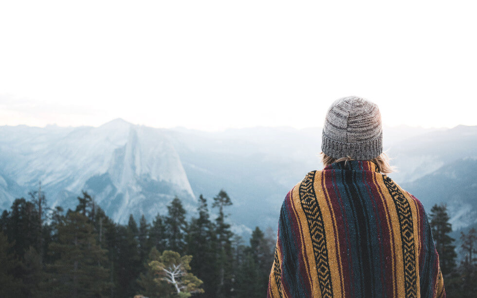 woman watching mountains in camping blanket