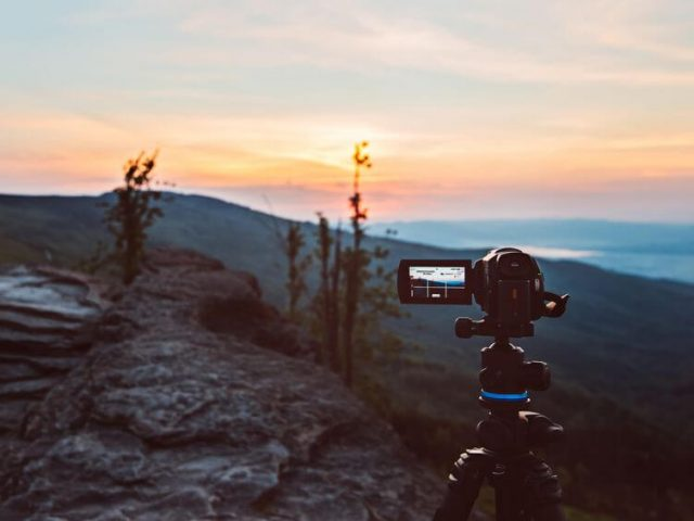 digital camera on tripod filming sunrise at mountains