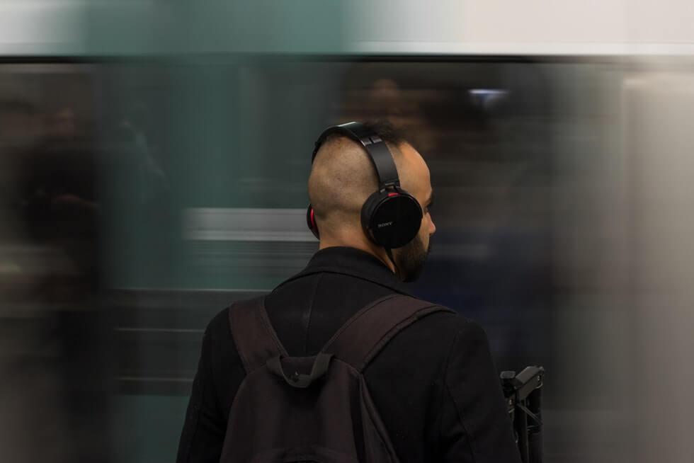 man wearing black headphones in metro station