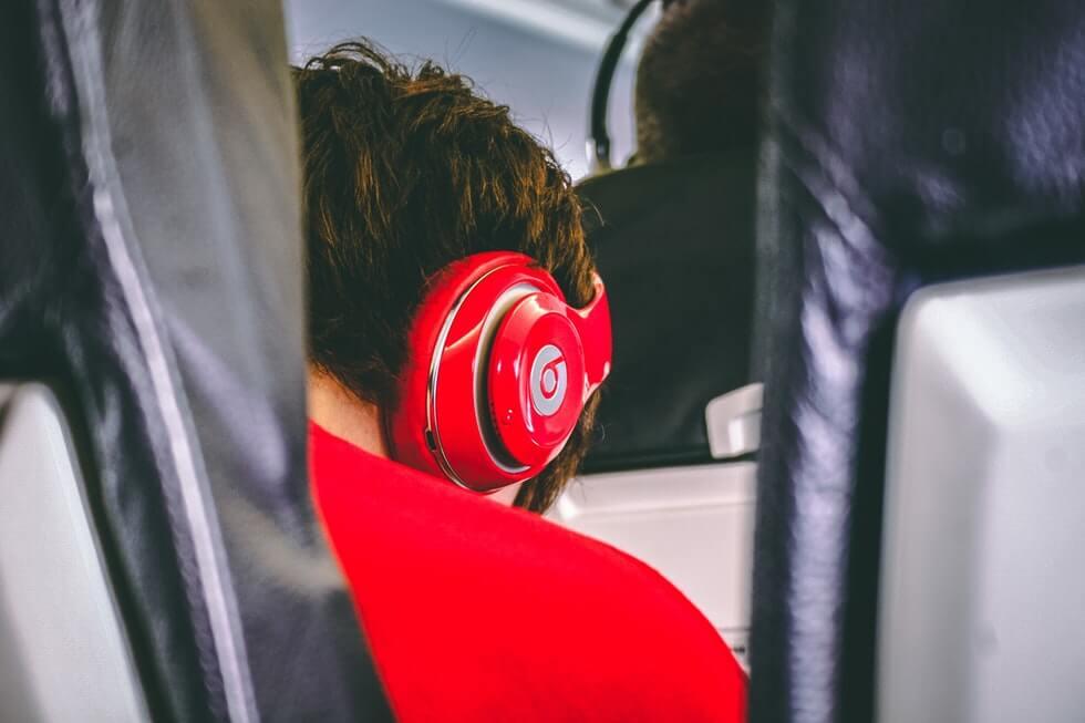 man wearing red headphones in airplane