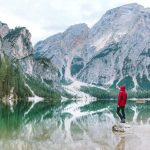 man wearing red hoodie and hiking pants standing near body of water