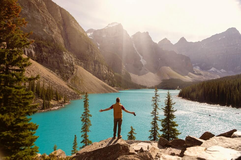 traveler standing on the cliff over a lake