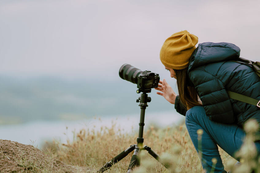 woman shooting with mirrorless camera at morning