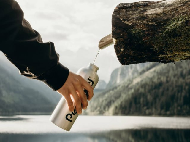 person holding gray reusable water bottle