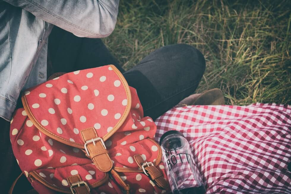 woman sitting with backpack and water bottle