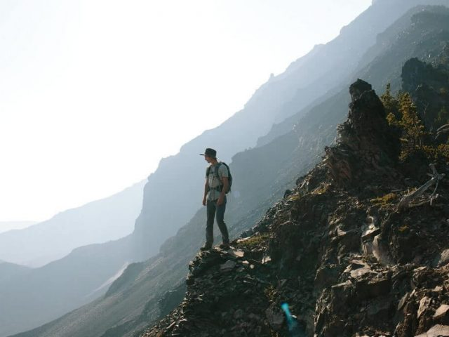 backpacker with hiking backpack in mountains