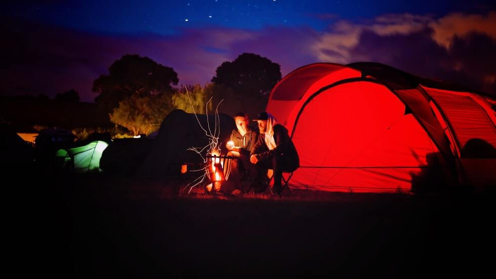 man and woman sitting beside bonfire and camping tent