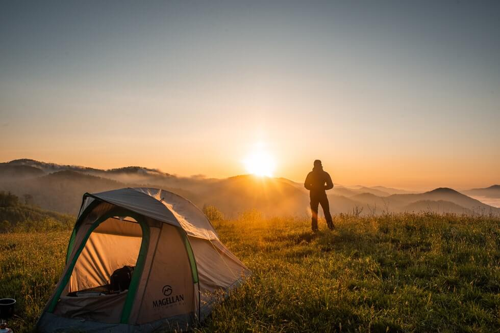 backpacker standing near camping tent