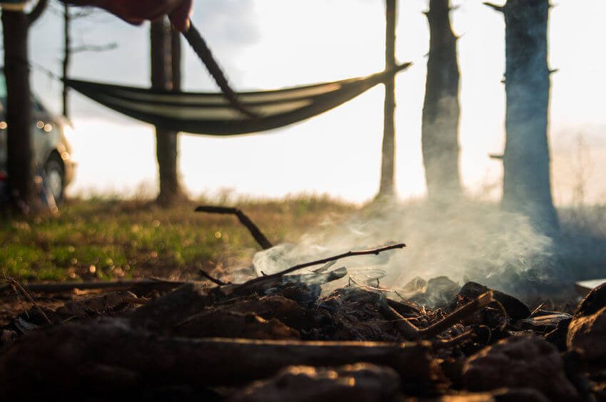 camping fire with hammock on the background